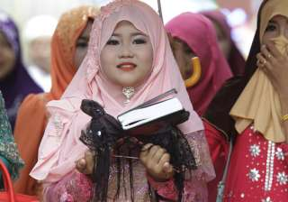 A girl carries a Quran during Eid al-Fitr prayers along the Mekong river of Tanong, northeast of Phnom Penh, Cambodia.