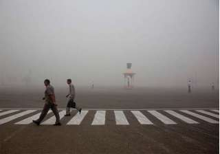 Indians walk to work as Delhi traffic police officers manage an intersection enveloped by smoke and smog, on the morning following Diwali festival in New Delhi, India, Monday, Oct. 31, 2016. As Indians wake Monday to smoke-filled skies from a weekend of festival fireworks for the Hindu holiday of Diwali, New Delhi's worst season for air pollution begins, with dire consequences. A new report from UNICEF says about a third of the 2 billion children in the world who are breathing toxic air live in northern India and neighboring countries, risking serious health effects including damage to their lungs, brains and other organs.