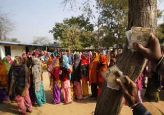 People hold their voter's identity card and wait in a queue to cast their votes at a polling station in New Delhi.