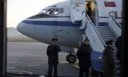 File - North Korean officials wait for passengers to board
