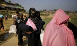 File - Rohingya Muslim women carry blankets and other