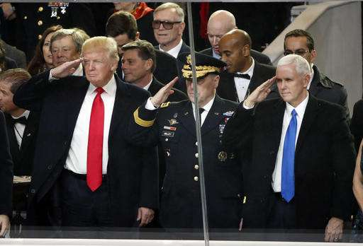 President Donald Trump salutes with Army Chief of Staff General Mark A. Milley and Vice President Mike Pence during the 58th Presidential Inauguration parade for President Donald Trump in Washington.
