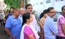 People queue up outside polling stations in Girinagar area