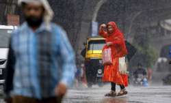 Thunderstorm Alert Latest News: A woman crosses a road amid