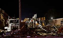 Emergency workers search through debris from a mobile home