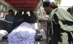 Afghans transport the body of a woman who was killed during