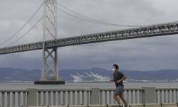 A man wears a mask to protect himself from the coronavirus while running in front of the San Franci