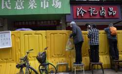 Residents climb on chairs to buy groceries from vendors behind barriers used to seal off a neighborh