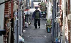 A man wearing a face mask to protect against the spread of the coronavirus, walks through an alley i