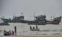 Fishing boats seen anchored at a shore following a warning