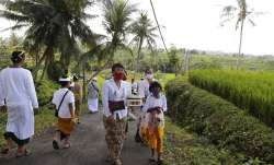People wearing face masks as a precaution against coronavirus outbreak walk to a temple at a village