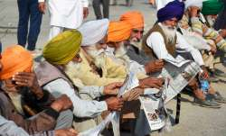 New Delhi: Farmers read newspapers at Singhu border during