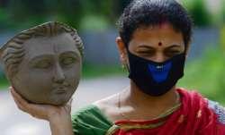 A woman artisan carries the face-idol of Goddess Durga at a studio in Agartala.