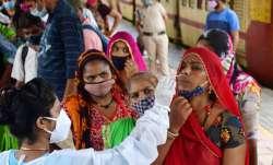 A medic collects nasal sample from a passenger at Dadar