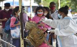 FILE| A health worker collects samples of passengers for