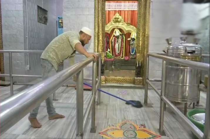 A Muslim man cleans and takes care of a Ram temple in