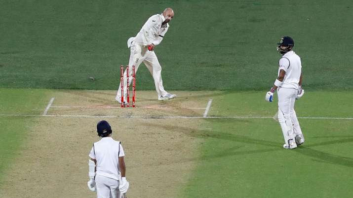 Nathan Lyon clips off the bails while Virat Kohli is in the